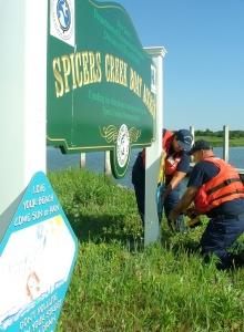 Auxiliarists hanging a sign on Spicers Creek Boat Access